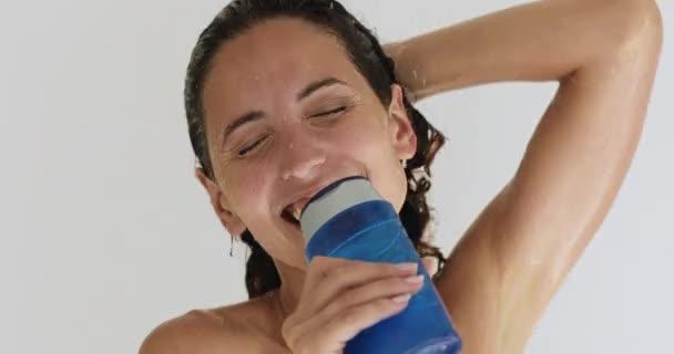 Nő éneklés használata sampon üveg, mint mikrofon, míg a zuhany
