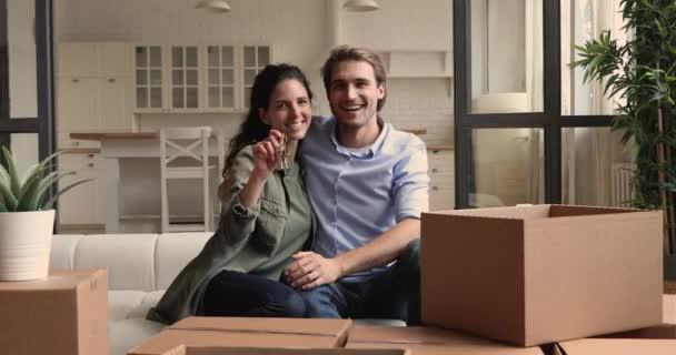 Feleség bemutató kulcsok ül férjjel a kanapén dobozok közelében