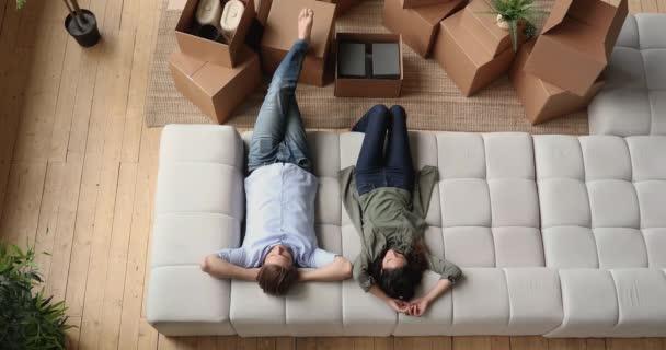 Pár odpočinku na gauči v den stěhování v novém domě