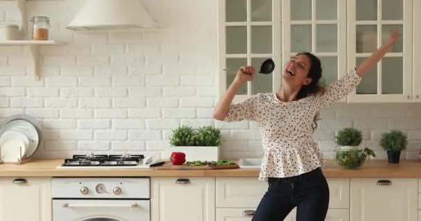 Fröhliche singende Frau benutzt Schöpfkelle wie Mikrofon in Küche