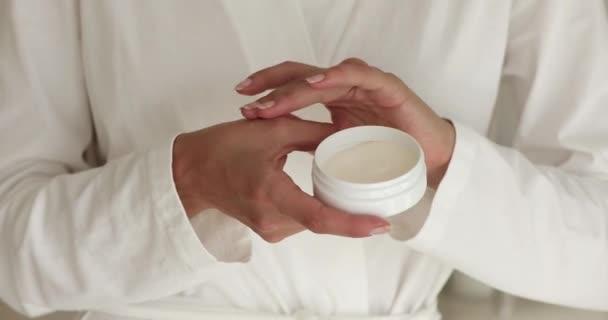 Žena v županu použít krém na ruce na kůži detailní pohled