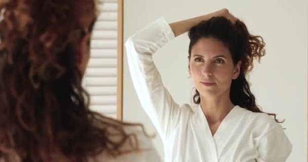 Pensive woman looking in mirror touch her curly hairs