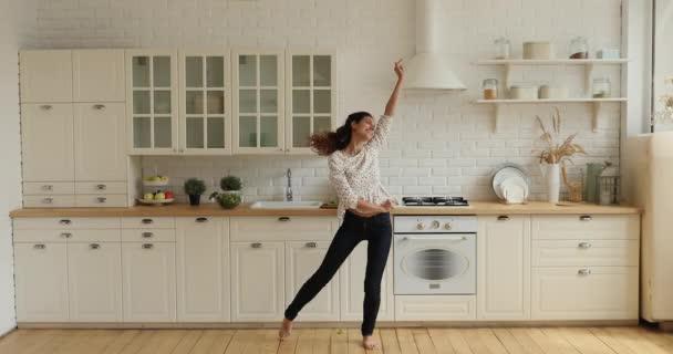 In moderner, geräumiger Küche singt und tanzt muntere Hausfrau barfuß