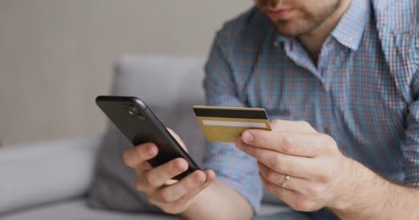 Konzentrierter junger Mann gibt Kreditkartendaten in Handy-App ein.