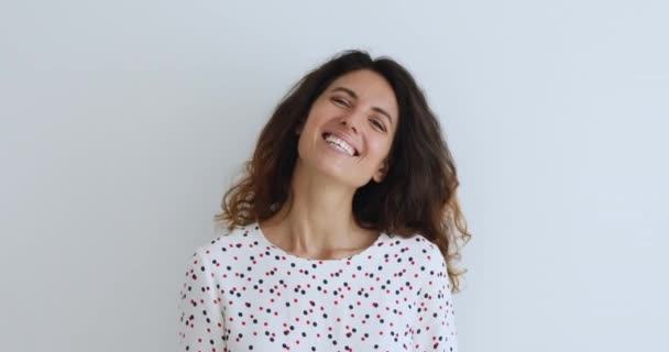 Atraktivní žena s kudrnaté vlasy smějící se pózování na šedém pozadí