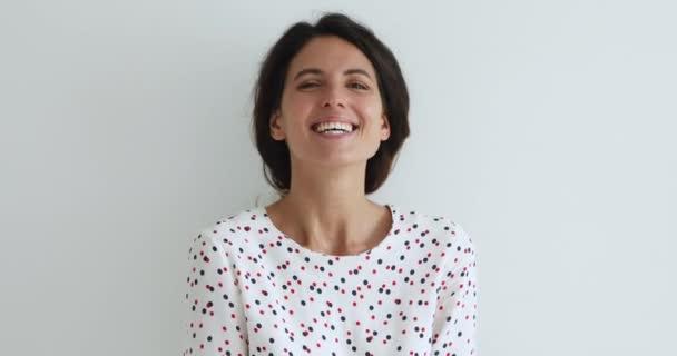 Veselá žena pózující v interiéru se dívá na kameru, směje se vtipu