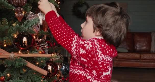 Kleine Kinder schmücken Weihnachtsbaum zu Hause