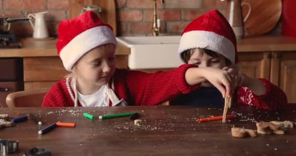 A kistestvérek asztalnál ülnek, és házi készítésű karácsonyi sütikkel játszanak.