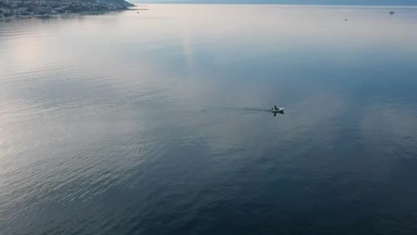 Fisherman on his boat moving in calm sea water at amazing morning for fresh mussels. Aerial bird view of coastal waters in Croatia.