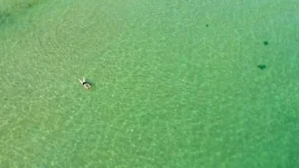 Lonely woman swimming in transparent sea water. Above the beach top view aerial