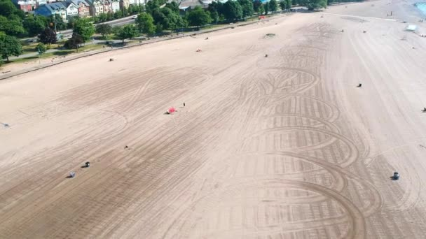 Aerial flying above water sandy beach coast on the sea shore with some people walking and enjoy the calm day near water. Drone gliding over.