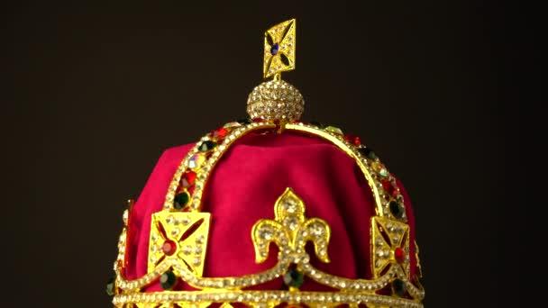 Diamantová koruna zhotovená ze zlata a červeného královského měkkého sametového materiálu pro slavnostní korunovaci na černém pozadí. Při pomalém otáčení pohyb s fokusem na horní okraj rámečku. 4k, UHD.