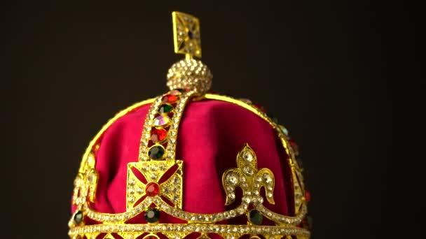 Diamantová koruna zhotovená ze zlata a červeného královského měkkého sametového materiálu pro slavnostní korunovaci na černém pozadí. Při pomalém otáčení se zaostřit na střed oblouků snímků. 4k, UHD.
