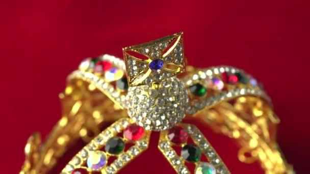 Corona di diamanti doro o accessorio decorativo da concorso da vicino messa a fuoco sulla parte superiore. Rotazione lenta sulla superficie rossa del colore reale. 4k