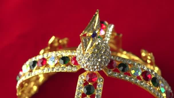 Arany gyémánt korona vagy dekoratív felvonás tartozék közelről összpontosítani az alsó keretben. Lassan forgás a piros királyi színes felületre. 4k, uhd.