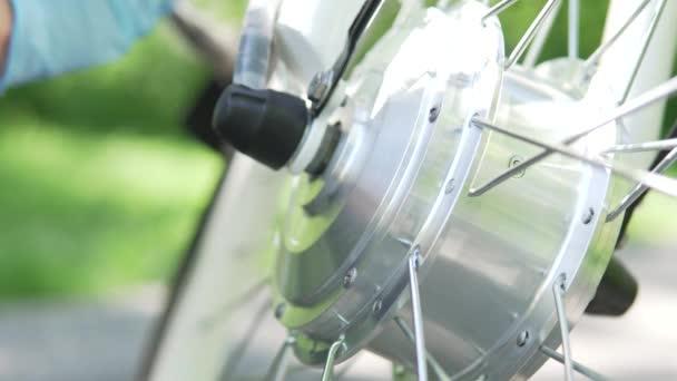 Radfahrer in blauen Handschuhen pflegen oder polieren den Reifen des Elektrorads mit Motor auf dem verschwommenen Hintergrund, draußen am Sommertag. konzentrieren sich auf den Motor. 4k
