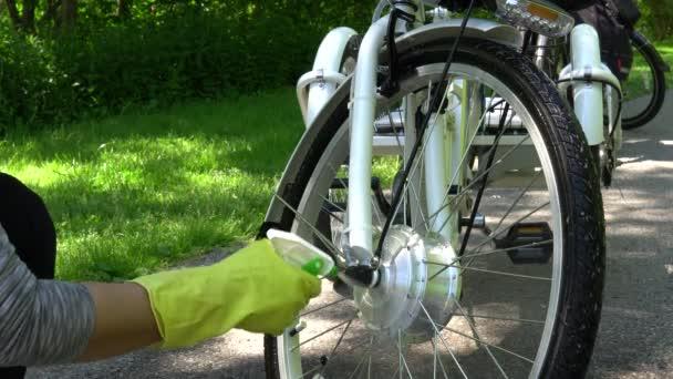 Radfahrer in gelben Handschuhen sprühen an Sommertagen draußen das Rad des Elektrofahrrads. Fahrer kümmern sich um das Sport E-Bike Rad mit Motor. 4k