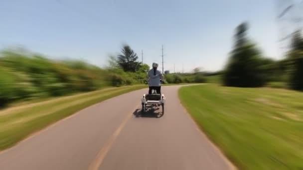 Fahrradpendler, die auf Straßen und Wegen mit Verkehr, Autos und Häusern mit dem E-Bike unterwegs sind. Geschwindigkeit Bewegungsunschärfe Hyperlapse oder Zeitraffer.