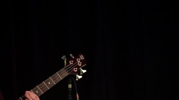 Férfi gitáros a színpadon egy koncerten játszott elektromos basszusgitár. A zenei hangszer bezárása. Gitáros találat a húrok a gitár a Rock fesztivál.