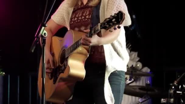 Közelről nő gitáros. Női gitáros találat a húrok a fa klasszikus gitár és a tánc a színpadon. Ügyes játék a zenei vonakodó régi hangszer rock koncert.