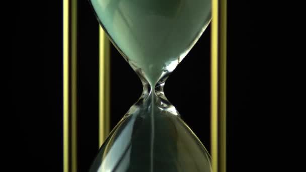 Forgó homokóra idő fogalom. Régi Vintage arany fém keret zöld homok óra lassan forog a sötét háttér. Közelről.