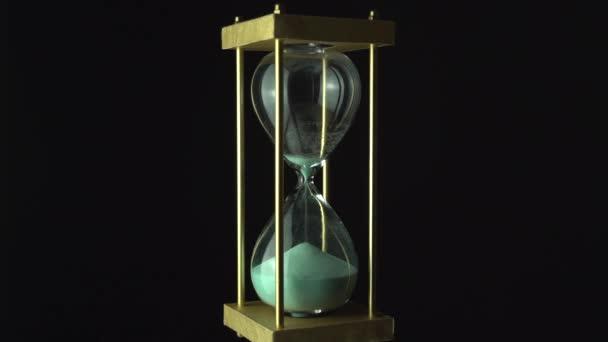 Még a homokóra óraidő fogalma. Régi Vintage arany fém keret zöld homok óra lassan forog a sötét háttér. Közelről.