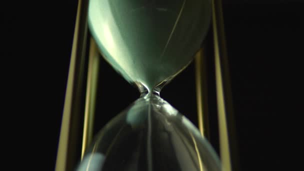 Homok üvegszemek a homokóra. Még mindig óra üveg közelről több mint fekete háttér, a mulandóság idő fogalom. Ideje minden élhető dolog ötlet.