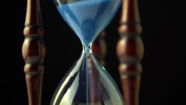 Rotating hourglass clock time concept. Old vintage wood frame blue sand clock slowly spinning on dark background. Close up.