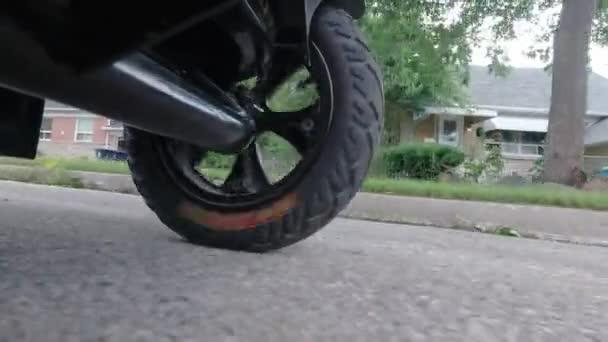 E-Bike fahren oder Elektroroller von unten schießen, Ökokonzept. E-Roller fahren durch Wohngebiet. Nahaufnahme des Hinterrades eines E-Bikes.