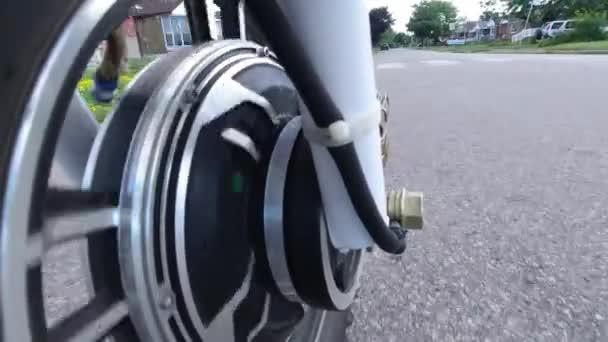 Nahaufnahme eines vorderen Motorrades, das sich unter der Motorhaube dreht, während man mit dem Elektroroller fährt. Blick von der Seite. Moderne alternative Verkehrsmittel, beliebte Mobilitätsoption.
