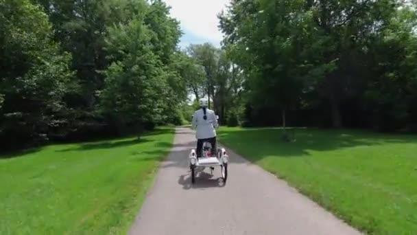 Egy nő a faluban elektromos kerékpárral a parkban a napsütéses nyári napon. Hátulról lőttek. Természetes világítás. A kilátás az akkumulátorra hátulról. Nyári szabadidős életmód.