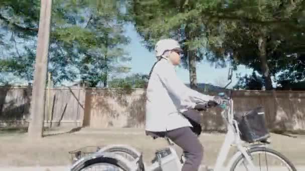 Zeitlupe der Frau im Helm, die an Sommertagen in der Stadt mit dem Elektrofahrrad unterwegs ist. Natürliches Licht. Ansicht der Batterie und des Motors von der Seite. Sommerlicher Lebensstil.