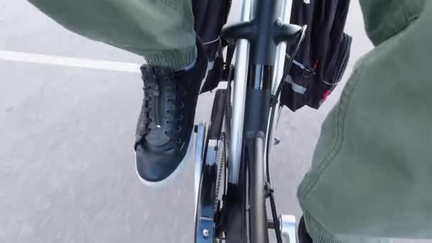 Cyklista kroutí pedály a jezdí na elektrickém kole s podporou pedálu. E kolo výstroj zblízka shora. Pohled na baterii na rámu. Cvičení a zdravý životní styl volného času.