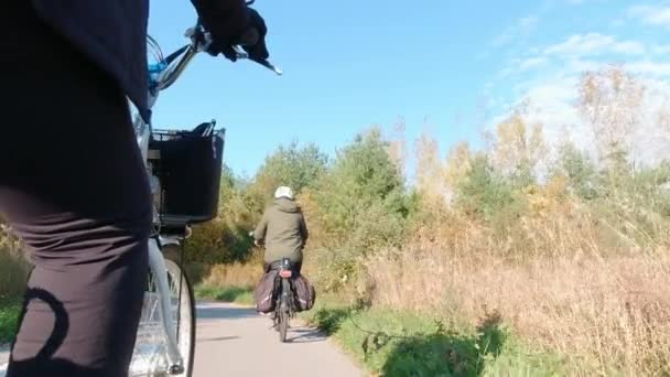 Radfahrer mit einem Elektrofahrrad auf der Grünfläche des Parks. Ökologiekonzept. Schuss von hinten.