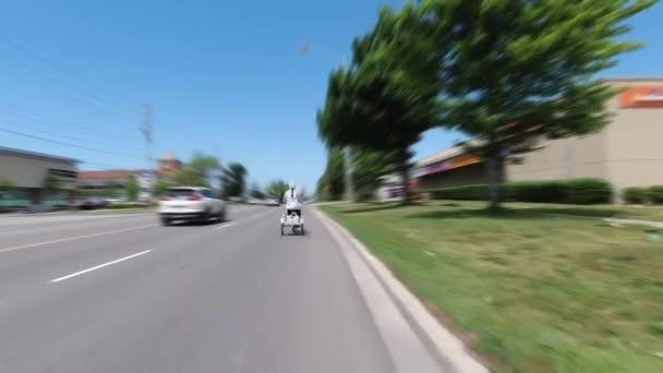 Elektronikus kerékpárral vagy elektromos kerékpárral, hátulról fotózva, ökológia koncepció. Egy nő elektromos triciklit vezet pedálozással. Alternatív motorenergia-szállítás.