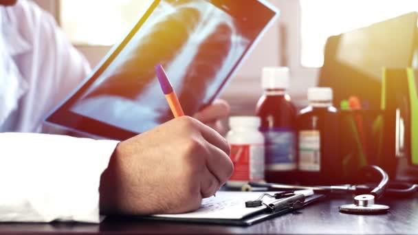 Arzt untersucht Röntgen-Scan und schreibt die Daten In einem medizinischen Formular