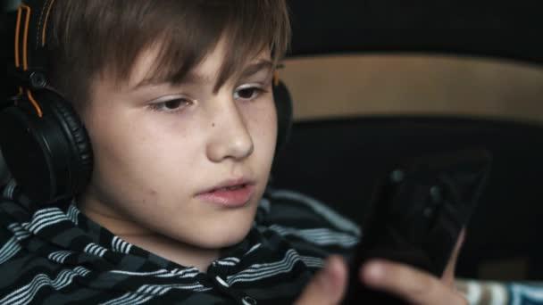 Portrét šťastný dospívající chlapec odpočíval s smartphone a sluchátka a poslech hudby doma. Děti, odpočinku a technologický koncept