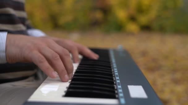 Hrát na klavír. Zblízka se mužských rukou, hraje na klavír. Prsty na klavíru