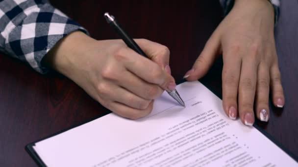 Nahaufnahme einer Geschäftsfrau, die die Seiten eines Papierdokuments oder eines Vertrages unterschreibt. Unterschrift auf einem Blatt Papier des Vertrages. Kugelschreiber bei der Unterschrift auf einem Blatt Papier des Vertrages