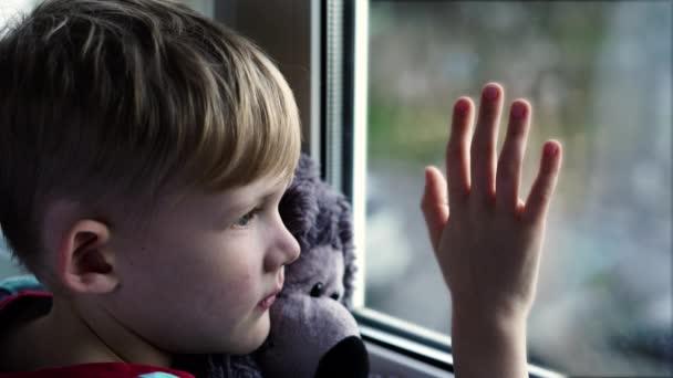 Malý chlapec zírá smutně z okna s plyšovým medvědem v náručí. Sedí na okenním parapetu. Dítě vypadá z okna.