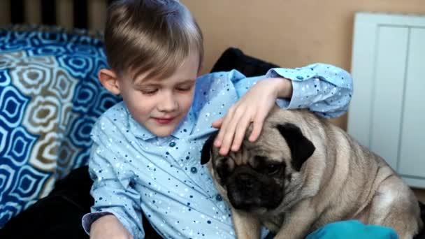 Junge spielt mit Mops-Hund im Haus auf der Couch
