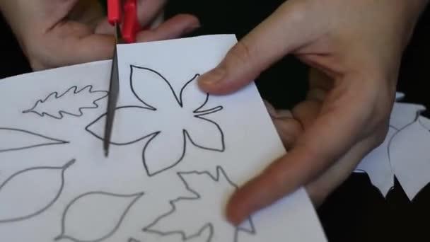 Vágása a fehér könyv a levelek a fák ollóval, rátétes és más kreativitás nyomtatott sablon