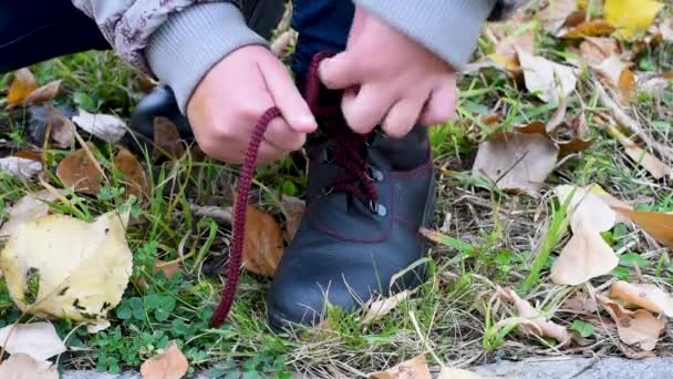 A child tying the red laces for black leather boots on a background of yellow leaves and green grass. When you walk the laces untied.