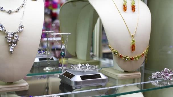 Šperky, přívěsky, prsteny, náušnice, náramky, náhrdelníky v okně dílny jiskřící paprsky z klesajících světel lamp