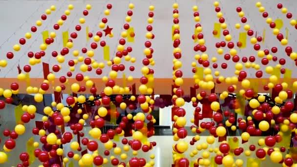 Červené a žluté zářivé korálky pro dekoraci a dekoraci visí na vodorovně natažených lanech v obchoďáku. Zábava se houpá od proudu vzduchu a vytváří slavnostní náladu