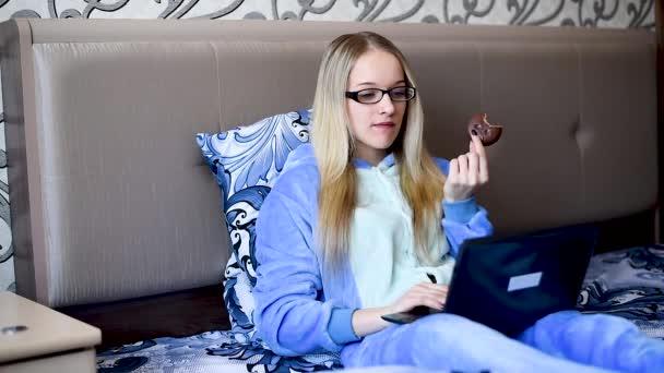 Blondine im Schlafanzug am Morgen an einem Ruhetag im Bett beim Kuchenessen mit einem Katzenmädchen im Bett am Morgen beim Dessert und beim Blick auf den Laptop
