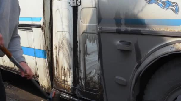 Mosás a busz után az út egy speciális kefével és vízzel. Egy ember mossa a piszkos busz a szabadtéri