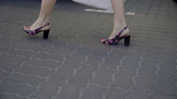 Ženské nohy. Ženské nohy jdou na asfaltu na patách