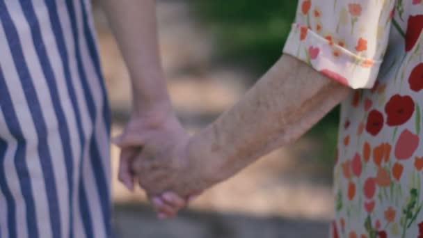 Nagymama és unokája tartsa kezét, és járni a parkban