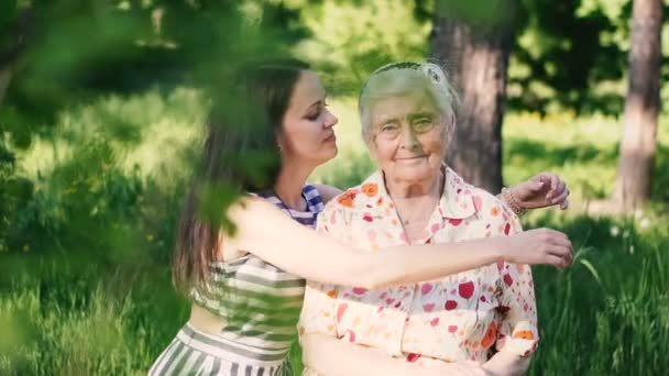 Enkelin umarmt ihre Großmutter und küsst sie auf die Wange